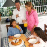 Hispanic family having breakfast in a kitchen. — Stock Photo #14397689