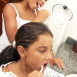 Two girls brushing their teeth. - Stockfoto