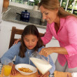 Hispanic mother pouring milk and cereal corn to her daughter. — ストック写真