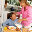 Hispanic mother pouring milk and cereal corn to her daughter. — Stock Photo