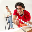 Hispanic couple working at new home. - Stock Photo