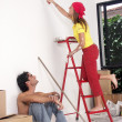 Hispanic couple painting a new house - Stok fotoğraf