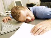 Exhausted young businessman sleeping at his desk — Stock Photo