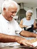 Grandparents enjoying and cooking together in a kitchen. — Stock Photo