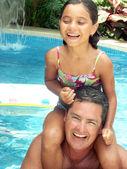 Hispanic father and daughter enjoying a swimming pool. — Stock Photo