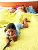 Dziewczynki oglądania tv w łóżku. — Zdjęcie stockowe