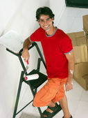 Young hispanic man moving to a new home. Young hispanic man painting a new home. — Stock Photo