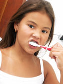 Little girl using a toothbrush. — Stock Photo