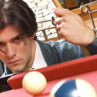 Young man plays billiards — Stock Photo #14609507