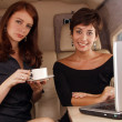Two women working inside a private jet — Stock Photo