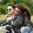 Couple enjoying a ride by motorcycle - Stock Photo