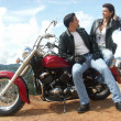 Young couple sharing in a motorcycle - Stockfoto