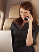 Businesswoman working on a private plane — Stock Photo