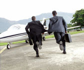 Two businessman running towards a plane — Stock Photo