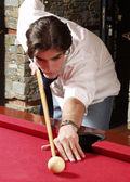 Young man plays billiards — Stock Photo