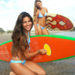 Women surfers on a beach. Two women holding a surfboard. - Stock Photo