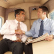 Business man shaking hands and working at private jet — Stock Photo