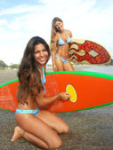 Women surfers on a beach. Two women holding a surfboard. — Stock Photo