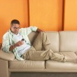 Relaxed young man lying down on sofa with a mobil phone. — Stock Photo #14625863
