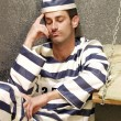 Depressed prisoner in a prison cell. Boring prisoner. - Stock Photo