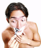 Happy and funny young man shaving his face over white background — Stock Photo