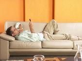 Ontspannen jonge man liggen op de bank met een mobil-telefoon. — Stockfoto