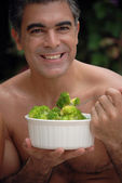 Young man eating vegetables behind a swimming pool. — Stock Photo