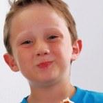Happy little kid eating brownie — Stock Photo