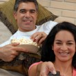 Couple watching tv and eating popcorn. Couple sharing in a living room. — Foto Stock
