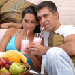 Mid adult couple drinking strawberry milkshake in a living room. — Stock Photo