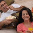 Couple watching tv and eating popcorn. Couple sharing in a living room. — Stock Photo