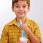 Little boy drinking strawberry milkshake — Stock Photo #14911317