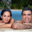 Latin couple enjoying together in a swimming pool. — Stockfoto