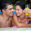 Young latin couple drinking orange juice in a swimming pool. — Stock Photo