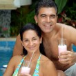 Latin couple drinking strawberry milkshake in a swimming pool. — Zdjęcie stockowe