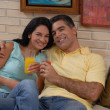 Mid adult couple drinking fruit juice in a living room. Couple drinking and sharing in a living room. — Foto de Stock
