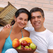 Mid adult couple eating fruits in a living room. — Foto Stock
