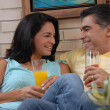 Mid adult couple drinking fruit juice in a living room. Couple drinking and sharing in a living room. — Stock Photo