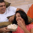 Couple watching tv and eating popcorn. Couple sharing in a living room. — Stock Photo #14912271