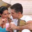 Mid adult couple drinking strawberry milkshake in a living room. — Foto de Stock