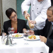 Hispanic couple at a restaurant and a waiter serving. — Stockfoto