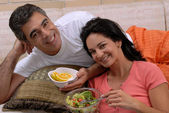 Mid adult couple eating salad and fruit in a living room. — Stock Photo