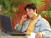 Young man using a laptop and talking on a mobile phone. — Stock Photo