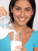 Young woman pouring milk glass. — Stock Photo