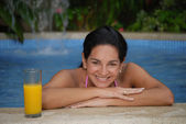 Hispanic woman relaxing in a swimming pool and orange juice glass. — Stock Photo