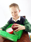 Little school kid holding a big red apple. — Stock Photo