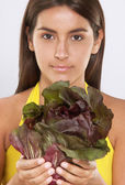 Young woman holding a radicchio bunch. — Stock Photo