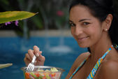 Young woman eating vegetables behind a swimming pool. — Stock Photo