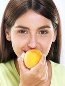 Mujer joven comiendo un melocotón — Foto de Stock