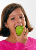Little girl holding and eating fresh apple — Stock Photo